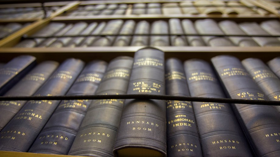 Looking up at a book shelf at many volumes of the Parliamentary Debates or Hansards.