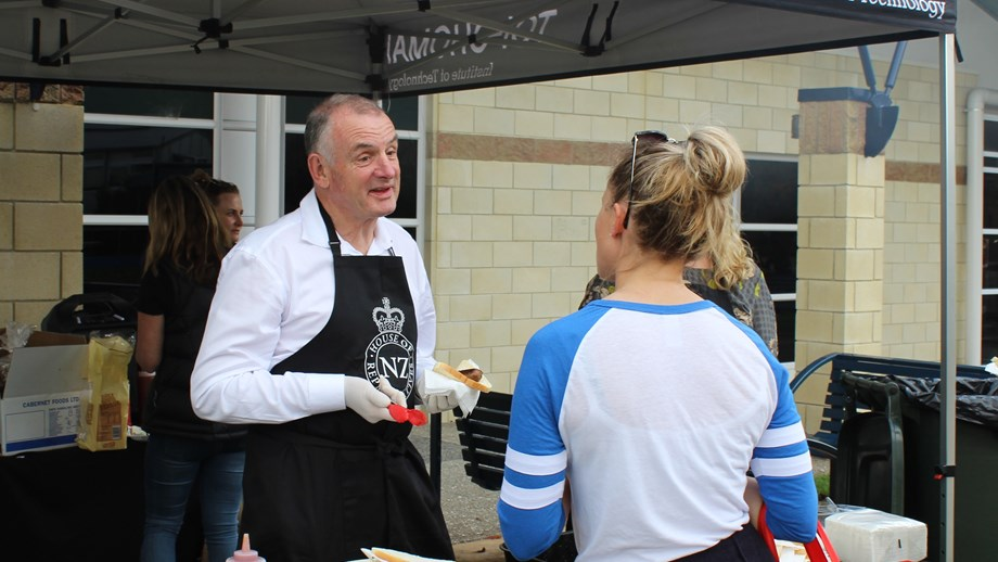 Speaker Trevor Mallard serving sausages at a BBQ during one of the Speaker Outreach events