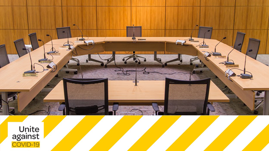 "An empty select committee room at Parliament with the yellow and black ""Unite against COVID-19"" banner running along the bottom of the image."