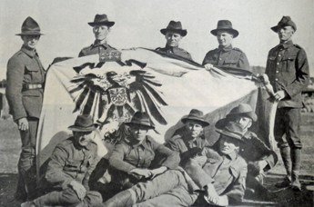NZ troops holding German flag captured in Apia, Samoa.